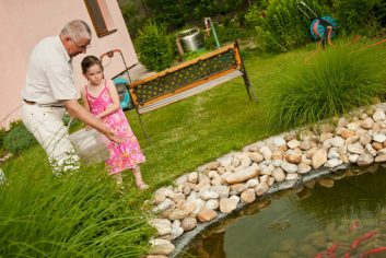 Grandparent-and-grandchild-standing-at-edge-of-fishpond